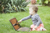 Cute baby girl using a laptop — Stock Photo