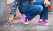 Child writing with chalk on schoolyard — Stock Photo