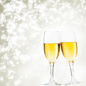 Champagne glasses against holiday lights — Stock Photo