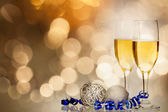 Champagne against holiday lights ang Christmas decorations — Stock Photo