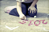 Girl writing 2015 with chalk — Stock Photo