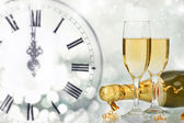 Glasses with champagne and bottle over sparkling holiday backgro — Stock Photo