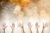 Painted palms with smiling faces celebrating New Year — Stock Photo