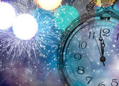 Vintageclock with fireworks and holiday lights — Stock Photo