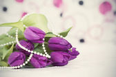 Purple tulips and necklace — Stock Photo