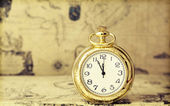 Pocket watch over antique map — Photo