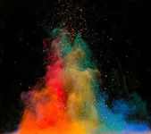 Launched colorful powder over black — Stock Photo