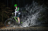 Mountain biker speeding through forest stream. — Zdjęcie stockowe