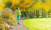 Young brunette woman running in park. — Stock Photo