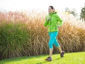 Young brunette woman running in park. — Stockfoto