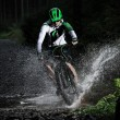 Mountain biker speeding through forest stream. — Stock Photo #57071393