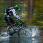 Mountain biker speeding through forest stream. — Stock Photo #57071439