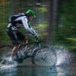 Mountain biker speeding through forest stream. — Stock Photo #57071453