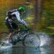 Mountain biker speeding through forest stream. — Stock Photo #57071469