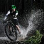 Mountain biker speeding through forest stream. — Stock Photo #57071499