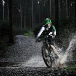 Mountain biker speeding through forest stream. — Stock Photo #57071527