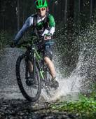 Mountain biker speeding through forest stream. — Stock Photo