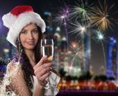 Young Santa girl with champagne glass — Stock Photo