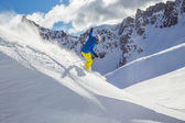 Skier skiing downhill in high mountains — Stock Photo