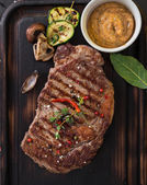 Beef rump steak on black stone table — Stock Photo