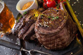 Beef rump steak on black stone table — Stock Photo
