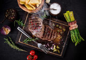 Beef steak on black stone table — Stock Photo