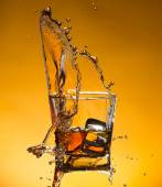 Whiskey with ice with liquid splash — Stock Photo