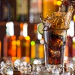 Glass of cola on bar desk with splashing liquid — Stock Photo #73039159