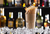 Cold coffee drink with ice, beans and splash — Stock Photo