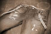 Holey jeans with suspenders, photo toning in sepia — Stock Photo