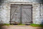 Large old wooden door in white stone building — Stockfoto
