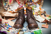 Men's leather boots standing next to crumpled scraps of paper - grunge style. Prestige autumn - spring shoes — Stock Photo
