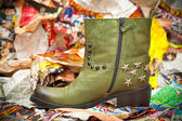 Women's green leather boots crumpled sheets of colored paper. grunge style. Autumn - spring shoes. Cowboy style - shoes with studs and stars — Stock Photo