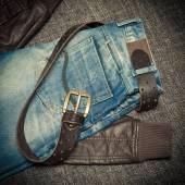 Fashion trend: blue frayed jeans, a leather jacket and leather belt with buckle — Stock Photo