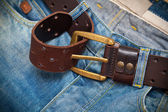 Tighten the leather belt with a buckle on jeans — Stock Photo