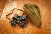 Military binoculars, forage cap with a red star. Victory Day on May 9. Retro style — Stock Photo