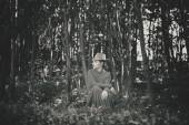 Girl in a dress and hat sitting on his haunches in the forest. Photo in retro style — Stock Photo