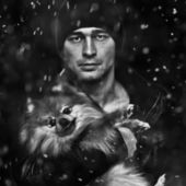 Portrait of a man with a dog on a black background, the snow falls — Stock Photo