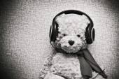 Plush teddy bear listening to music on headphones. Vintage discolored Photo — Stock Photo