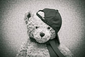 игрушечный плюшевый мишка, носящий шарф и бейсболку — Стоковое фото