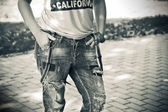 Female figure close-up: ripped jeans worn with suspenders, shirt, a bracelet on her arm — Stock Photo