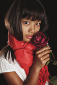 Studio portrait of a girl of Asian ethnicity in a red scarf with burgundy rose in her hand — Stock Photo
