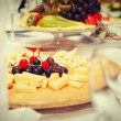 Covered table in the restaurant - cheese plate, fruit plate — Stock Photo #66228279