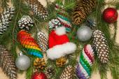 Christmas or New Year decoration background: fur-tree branches, colorful glass balls, colorful fir cones and Santa Claus hat — Stock Photo
