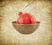 Pomegranate in the ancient carved vase over old paper background in vintage style — Stock Photo