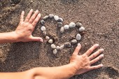 Woman's hands making heart of marine shingles on the sand. — Stockfoto