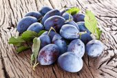 Plums on an old wooden table. — Stock Photo