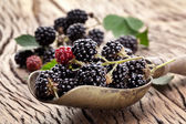 Blackberries with leaves on a old wooden table. — Stock Photo