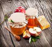 Glass cans full of honey, apples and combs. — Stock Photo