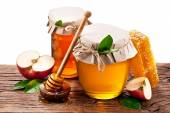 Glass cans full of honey, apples, honeycombs old wooden table. F — Stock Photo